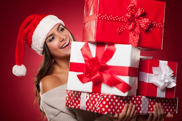Nette junge frau, die weihnachtsmütze hält weihnachtsgeschenke hält