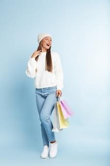 Nette junge frau, die wintermütze trägt und einkaufstaschen hält.