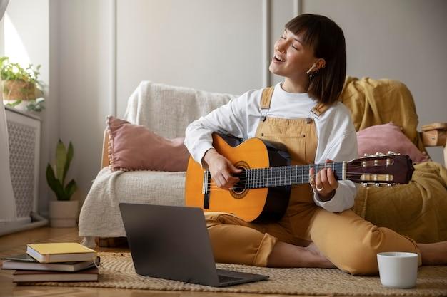 Nette junge frau, die zuhause gitarre spielt