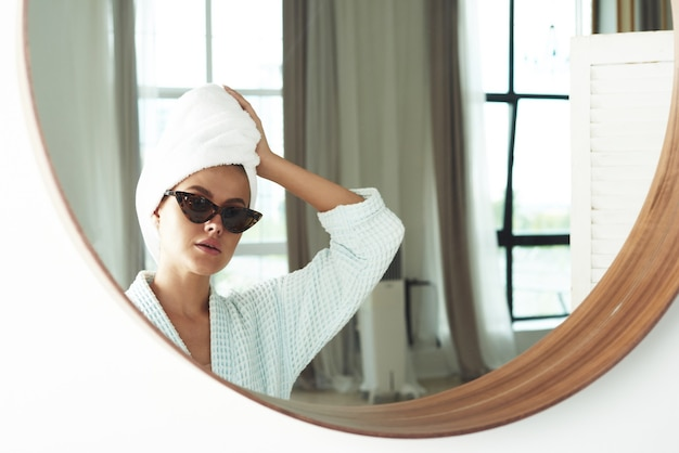 Nette junge frau im bademantel, mit einem weißen handtuch auf dem kopf und einer schwarzen sonnenbrille, die vor dem badezimmerspiegel herumalbert.