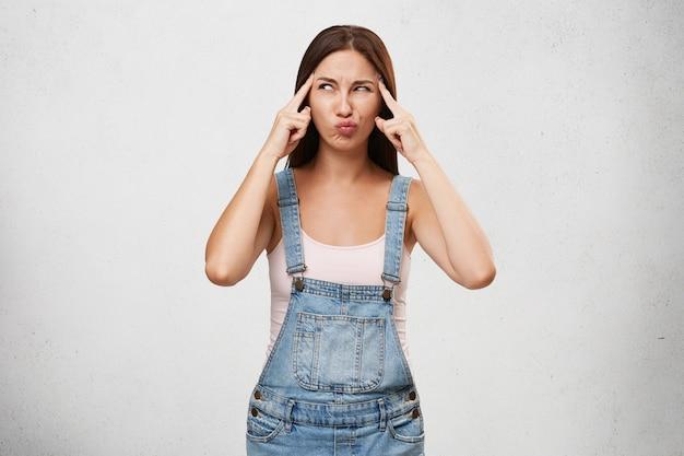 Nette junge frau im jeansoverall, die finger an ihren schläfen hält und mit konzentriertem ernstem ausdruck seitwärts schaut, während sie nach lösung für persönliche probleme oder probleme bei der arbeit sucht