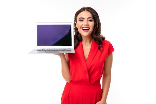 Nette junge frau im roten kleid hält netzwerk mit modell mit bildschirm vorwärts auf weiß