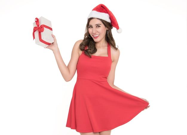 Nette junge frau im roten kleid sankt, die geschenkbox für weihnachten lokalisiert auf weißem hintergrund hält.