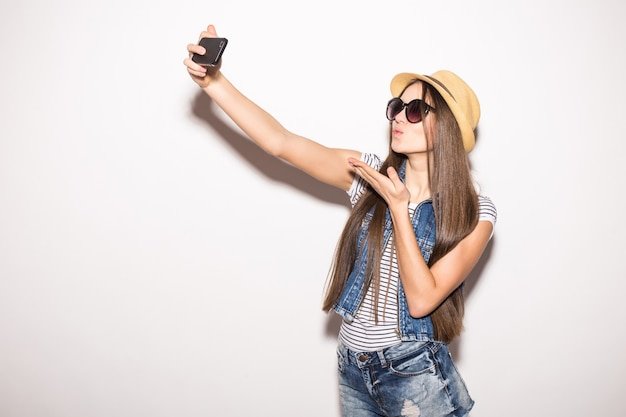 Nette junge frau im strohhut und in der sonnenbrille, die selfie mit handy nimmt