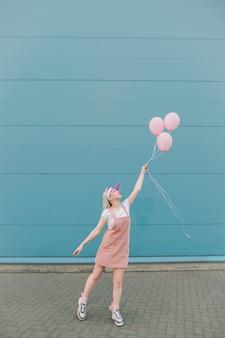 Nette junge frau in den rosa kleidern, die mit luftballons stehen