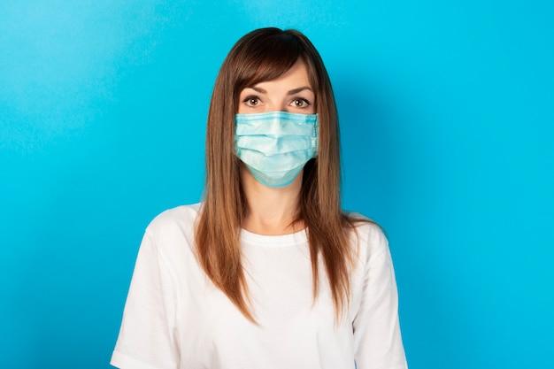 Nette junge frau in der medizinischen schutzmaske und im weißen t-shirt auf blau. persönliches virenschutzkonzept, krankheit, virus, epidemie, pandemie