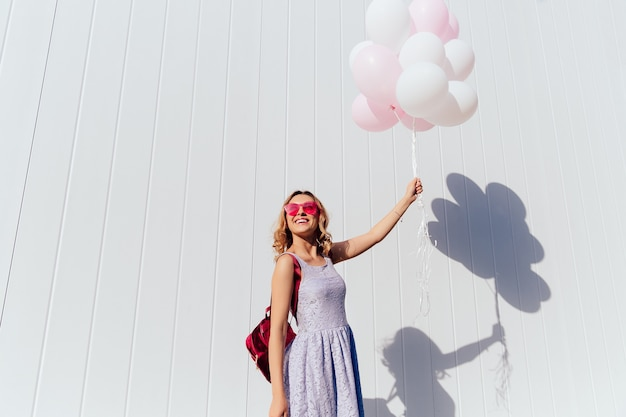 Nette junge frau in der rosa sonnenbrille den sonnigen tag genießend und halten luftballone