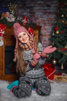 Nette junge frau in einem hässlichen pullover neben einem weihnachtsbaum, zieht wollhandschuhe an