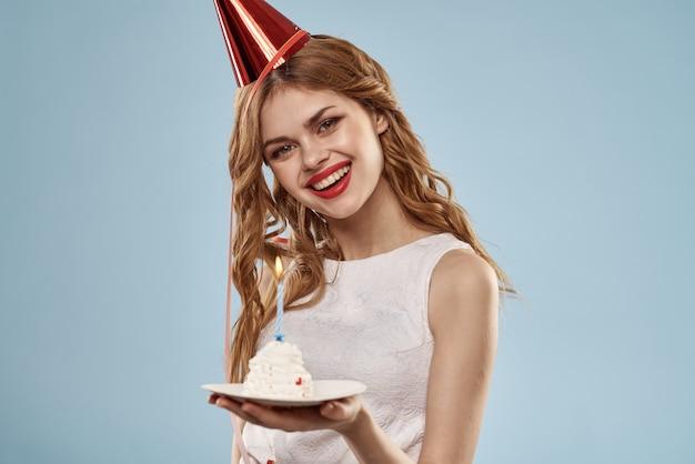 Nette junge frau mit einem cupcake und kerzen feiert geburtstag, studio, blauen hintergrund