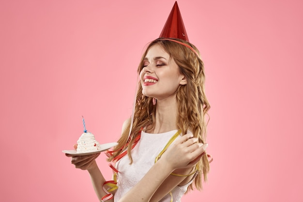 Nette junge frau mit einem cupcake und kerzen feiert geburtstag, studio, rosa hintergrund