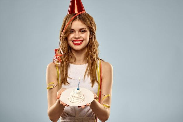 Nette junge frau mit einem cupcake und kerzen feiert geburtstag