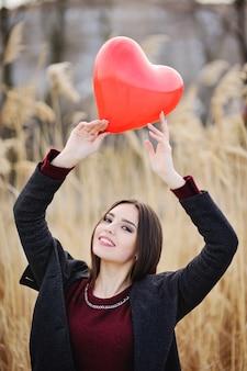 Nette junge frau mit einem roten luftballon auf einem gebiet