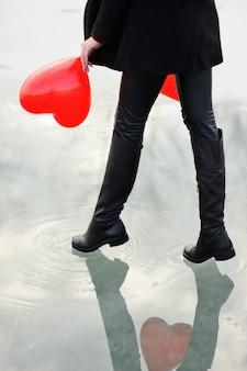 Nette junge frau mit einem roten luftballon