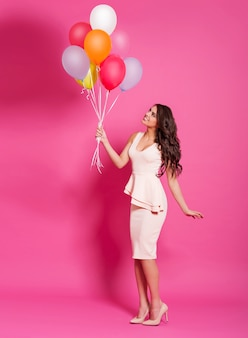 Nette junge frau mit luftballons