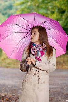Nette junge frau mit regenschirm