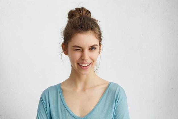 Nette junge frau mit zarten gesichtszügen, die haare im knoten gebunden tragen und blauen pullover tragen, der ihre augen mit vergnügen blinzelt, das glücklichen ausdruck hat