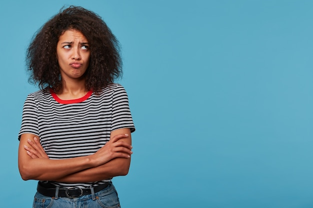 Nette junge frau sieht beleidigte verärgerte schmollende lippen aus, die mit verschränkten armen in gestreiftem t-shirt stehen