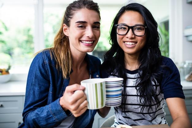 Nette junge freundinnen, die kaffeetasse halten