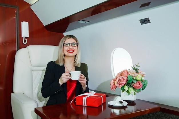Nette junge geschäftsfrau mit geschenkfliegen im luxus-privatjet
