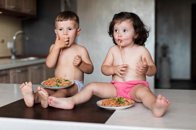 Nette junge geschwister, die teigwaren essen