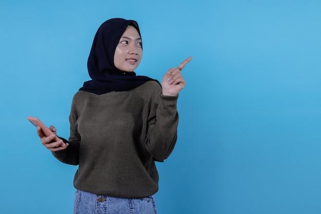 Nette junge hübsche frau, die mit dem handy hält, das hijab trägt