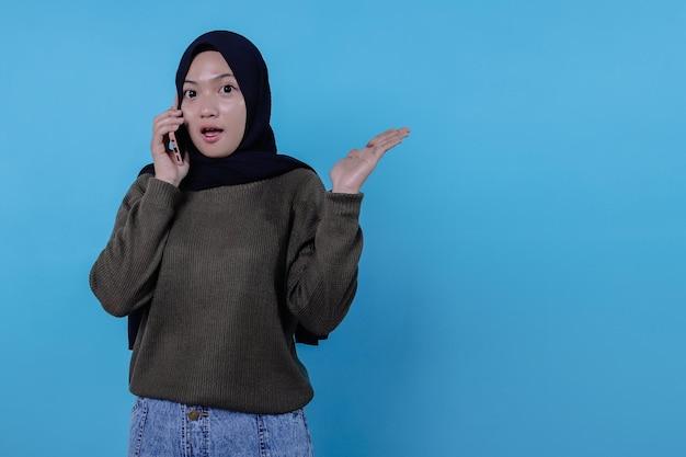 Nette junge hübsche frau, die per handy mit hijab anruft