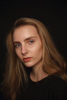 Nette junge hübsche frau mit langen haaren im hemd posiert auf schwarzem hintergrund