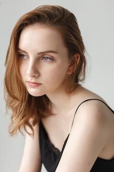 Nette junge hübsche frau mit langen haaren im schwarzen top posiert auf weißem hintergrund