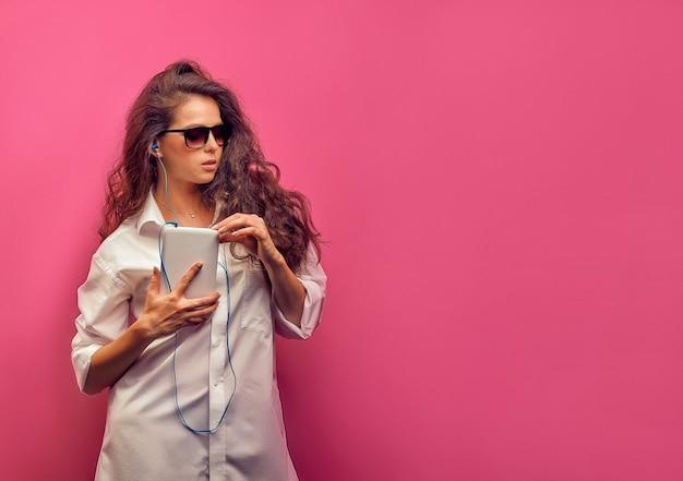 Nette junge kaukasische brünette frau in einem weißen hemd in den gläsern mit kopfhörern, die eine weiße tablette in den händen auf einer rosa hellen wand halten.