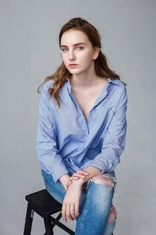 Nette junge kaukasische hübsche frau mit langen haaren im blauen hemd und zerrissenen jeans