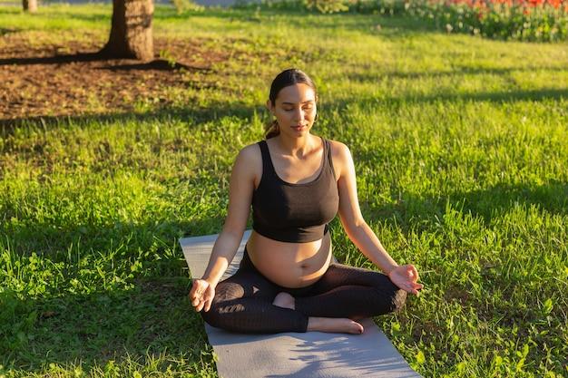 Nette junge kaukasische schwangere frau meditiert, während an einem sonnigen tag auf einem teppich auf dem rasen sitzend