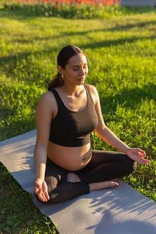Nette junge kaukasische schwangere frau meditiert, während sie auf einem teppich auf dem rasen sitzt