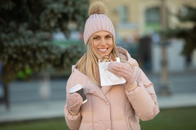 Nette junge kaukasische teenagerfrau in beigem hut mit pompon und rosa handschuhen, die dampfenden tasse heißen tee oder kaffee halten, im freien im sonnigen wintertag.