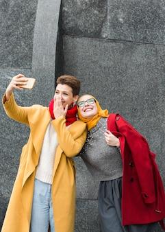 Nette junge mädchen, die zusammen ein selfie nehmen