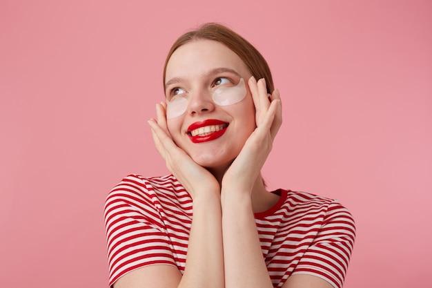 Nette junge rothaarige dame mit roten lippen, in einem rot gestreiften t-shirt, sehr erfreut über neue flecken aus dunklen ringen unter meinen augen, berührt sein gesicht mit den fingern, steht.