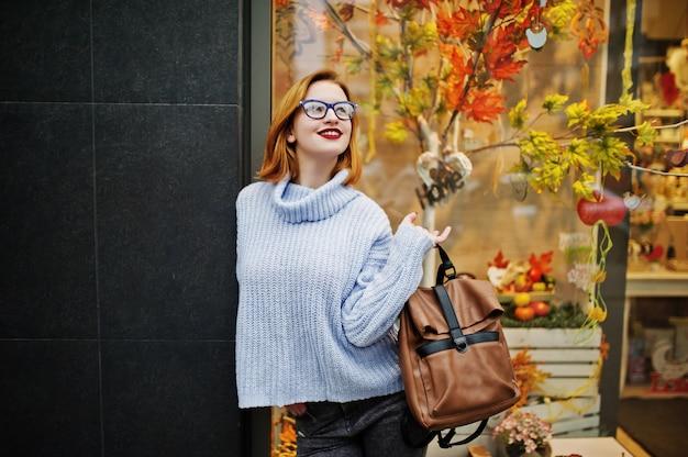 Nette junge schöne redhaired frau in den gläsern, warme blaue wollstrickjacke mit rucksack warf im freien gegen herbstlaubbaumdekorationen auf speicher auf.