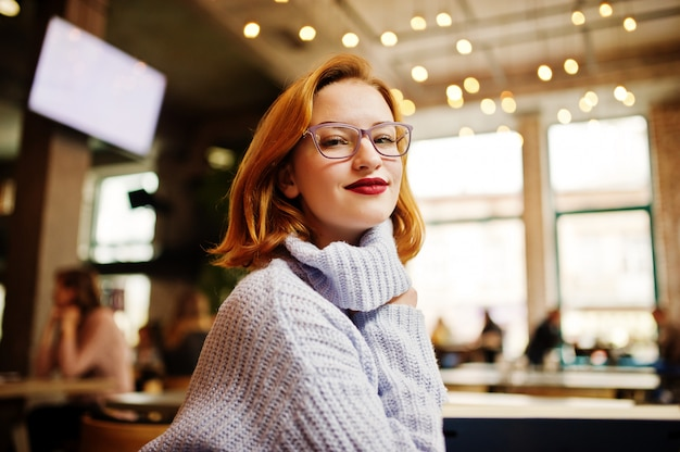 Nette junge schöne redhaired frau in den gläsern, warme wollstrickjacke, die an ihrem arbeitsplatz auf café sitzt.