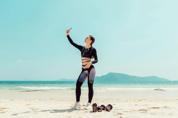 Nette junge sportlerin mit den kopfhörern, die ein selfie mit den ausgestreckten händen bei der stellung am strand nehmen. phuket. thailand. sommerferien und sportliche aktivitäten