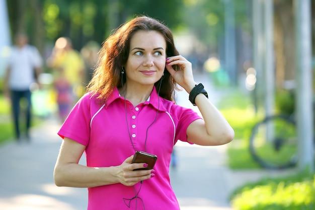 Nette junge sportliche frau, die musik auf einem spaziergang hört