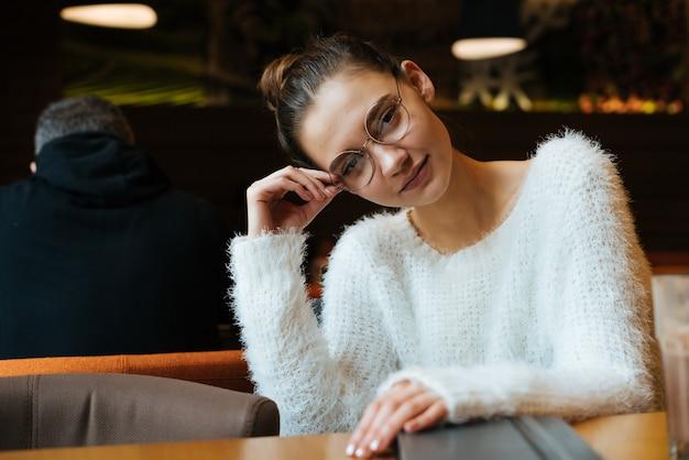 Nette junge studentin, die eine brille trägt und einen weißen pullover trägt, der nach der schule in einem café sitzt?