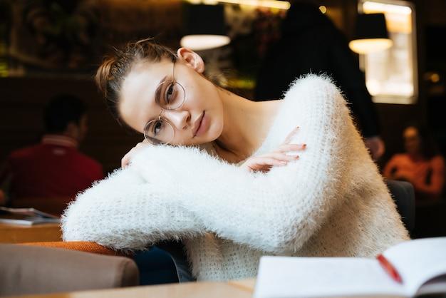Nette junge studentin in einer weißen jacke und brille, die nach der schule in einem café sitzt