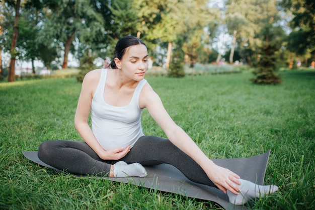 Nette junge übung der schwangeren frau im park draußen. sie erreicht füße mit einer hand. ein anderer hielt sich am bauch fest. das model ist ruhig und friedlich. sie sitzt auf yoga-kumpel.