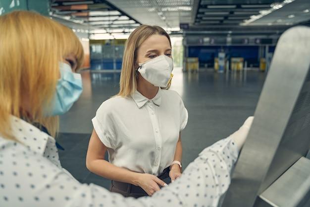 Nette junge weibliche person, die maske trägt, während sie am flughafen ist und sich auf ihren flug vorbereitet