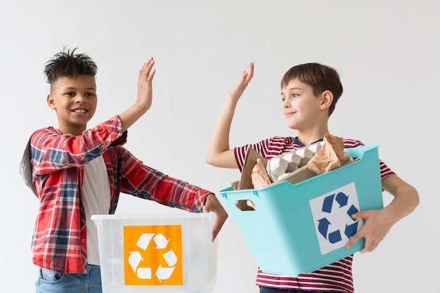 Nette jungen, die glücklich sind, zusammen zu recyceln