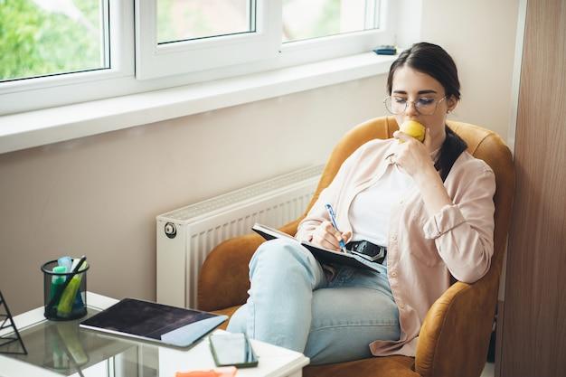 Nette kaukasische dame mit gesunden gewohnheiten isst einen apfel, während sie etwas in das buch schreibt und mit einer tablette arbeitet