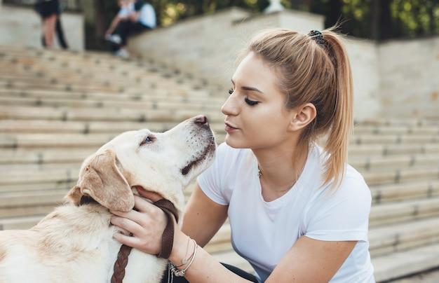 Nette kaukasische frau, die ihren goldenen retriever küsst, während sie draußen geht