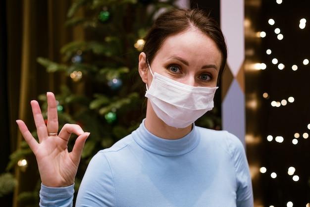 Nette kaukasische frau in einer medizinischen maske zeigt mit einer geste, dass alles vor dem hintergrund von bokeh und weihnachtsbaum in ordnung ist