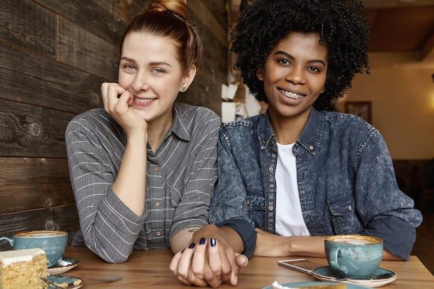 Nette kaukasische frau mit haarknoten, die hand ihrer stilvollen afrikanischen freundin während des mittagessens hält