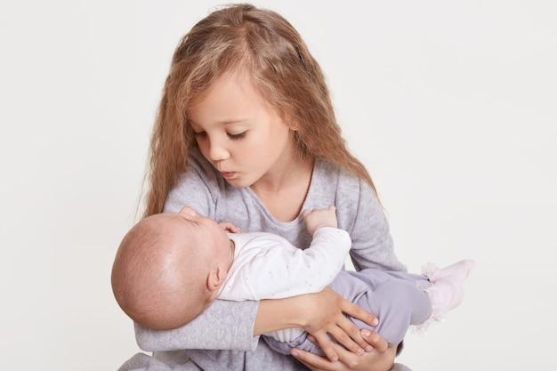 Nette kaukasische mädchenschwester, die kleines baby drinnen hält. älteres geschwister mit jüngerer schwester neugeborener. familienliebe, die zusammenbindet, blondes charmantes weibliches kind, das baby mit liebe betrachtet, lokalisiert auf weiß.