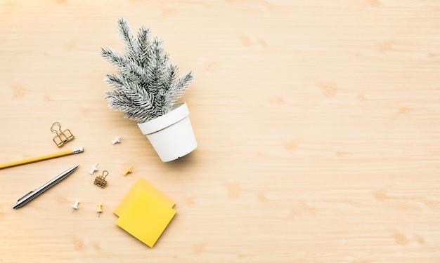 Nette kiefer verspotten in weißem topf und zubehör, das auf hölzernem arbeitstischhintergrund stationär ist. frohe weihnachts- und winterkonzeptideen. minimaler stil